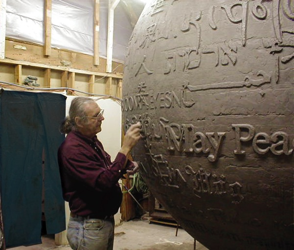 Hank working on the clay. Each letter of each prayer was hand made on the big clay/steel ball.